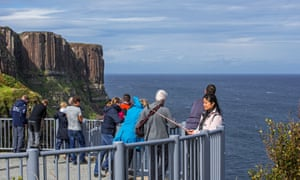 Tourists at a viewpoint looking at Mealt waterfall at Kilt Rock on Skye.