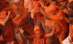 Revellers in Thima throw vermillion powder