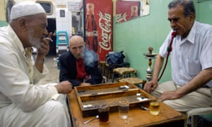 Men smoking and playing backgammon at a bar in downtown Amman.