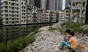 Children play among the wreckage of houses in Xian village, a slum area in downtown Guangzhou.
