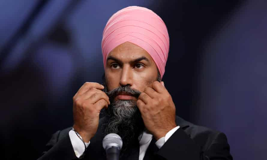 Jagmeet Singh wearing the Sikh dastar and gesturing with both hands at the microphone