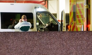 A paramedic changes into protective clothing in London.