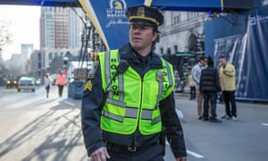 Mark Wahlberg on a street, in a high-viz jacket and police cap, in a  scene from Patriots Day