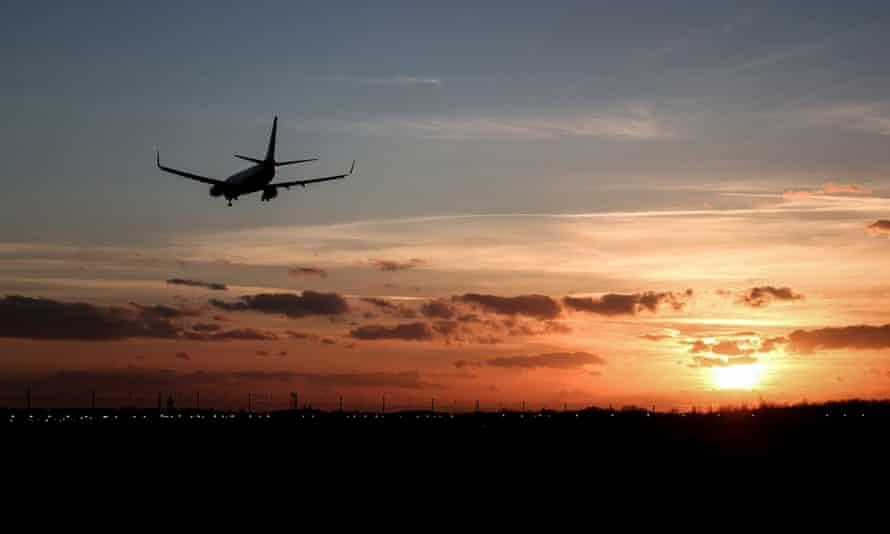 Boeing 737 airliner landing at sunset