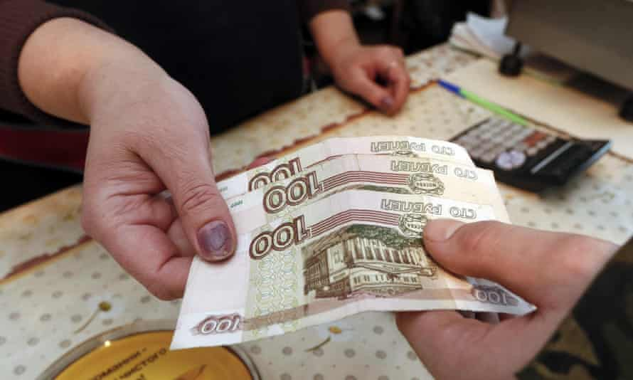 A customer hands over 100-rouble banknote