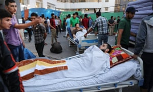 The wounded sit in a parking area outside of Gaza's main hospital due to an overflow of patients in Gaza City