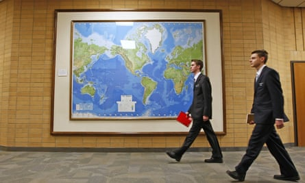 Two Mormon missionaries walk past a map of the world at the missionary training centre in Provo, Utah. Mormon missionaries will remain in Russia despite a new anti-terrorism law, which will put greater restrictions on religious work.