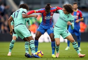 Zaha fends off Iwobi and Guendouzi.