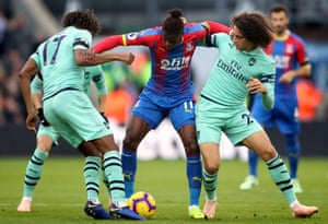 Crystal Palace's Wilfried Zaha holds off both Arsenal's Alex Iwobi and Matteo Guendouzi during the 2-2 draw at Selhurst Park.
