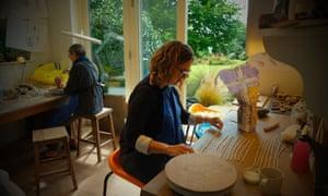 A studio shot showing two women at desks making pottery
