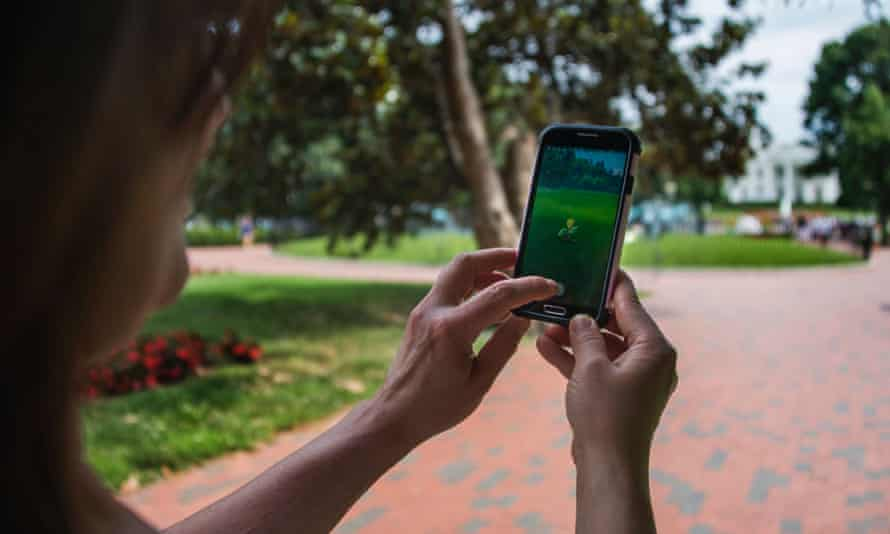 A woman holds up her mobile phone as she plays Pokémon Go.