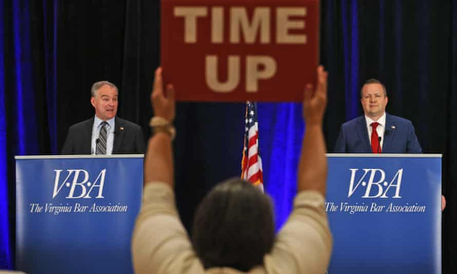 A time keeper holds a sign as Tim Kaine, left, and Republican challenger Corey Stewart, right, debate in Hot Springs, Virginia.