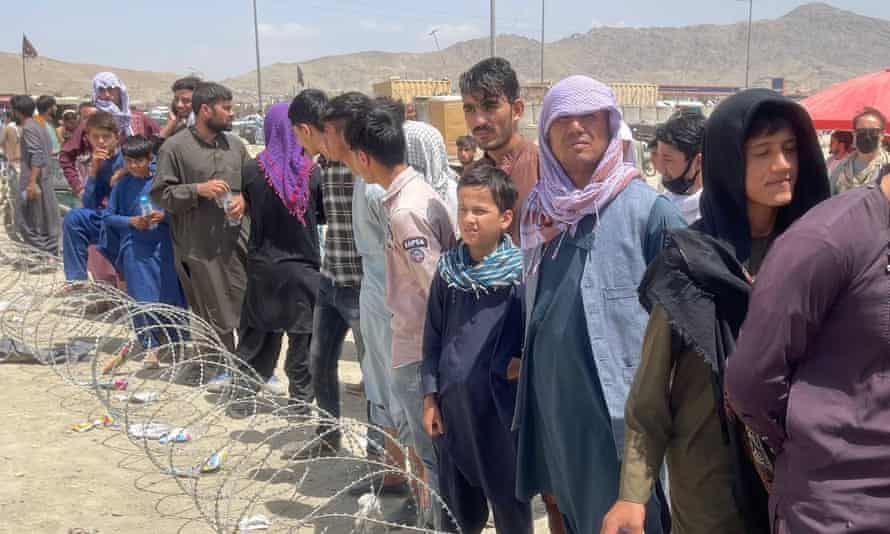 Afghans continue to wait around the Kabul international airport as they try to flee the Afghan capital on Friday.