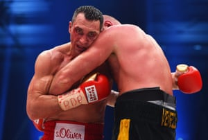 A bloodied Wladimir Klitschko clinches Tyson Fury.