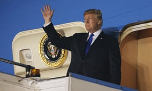 Donald Trump waves as he steps off Air Force One