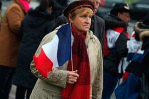 A woman holds a French flag outside the Invalides, during a ceremony honoring those killed.