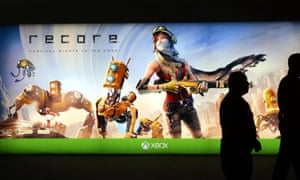 Two police officers are silhouetted against a luminous banner advertising action-adventure video game Recore.
