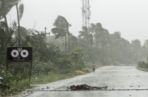 A farmer lies on the road after falling while crossing in winds ahead of cyclone Fani's landfall