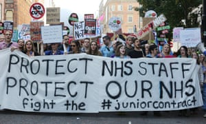 The front of a protest march; many people hold a large banner reading 'protest NHS staff, protect our NHS fight the #juniorcontract'.