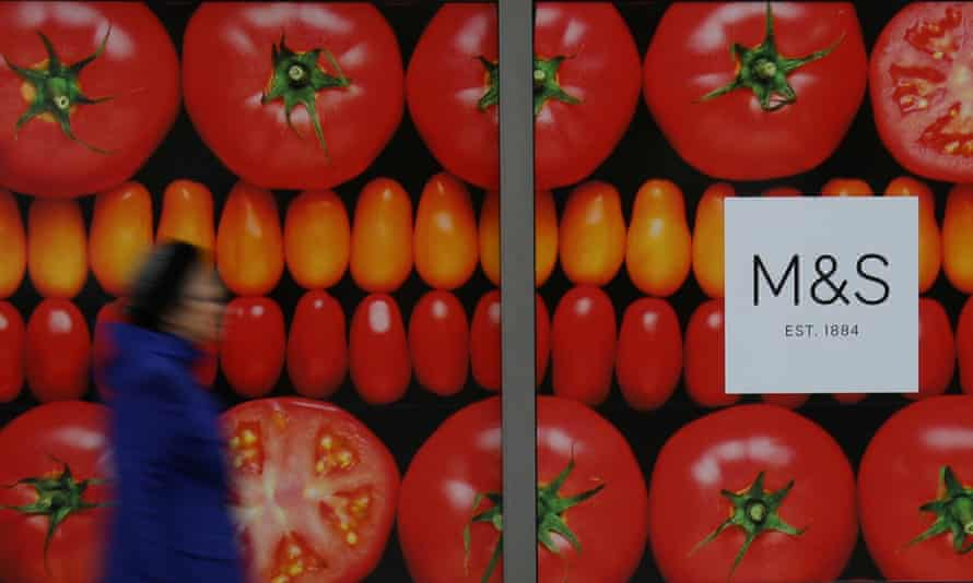 A woman passes an M&S shop window poster of rich red ripe tomatoes