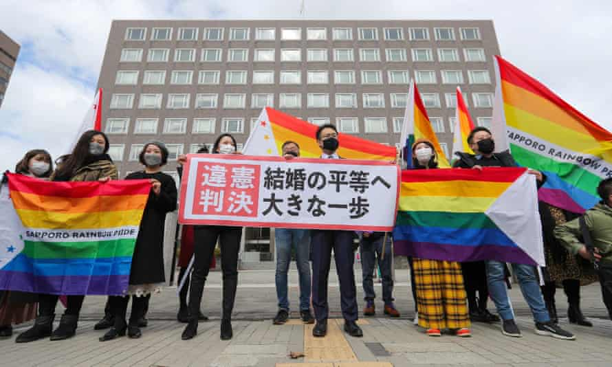 Supporters hold a sign reading 'unconstitutional decision' as they celebrate Sapporo district court's decision