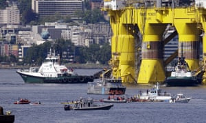 A small flotilla of kayakers and other protest boats follow as the oil drilling rig Polar Pioneer is towed toward a dock on Thursday in Elliott Bay in Seattle.