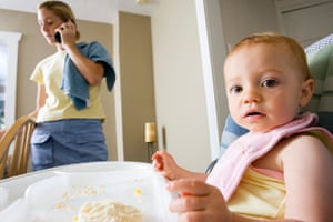 Baby girl (18-21 months) sitting in highchair, mother on mobile phone