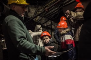 Irek, a former miner (left) turned tour guide, leads a group of children through the Guido deep coalmine in Zabrze, Silesia