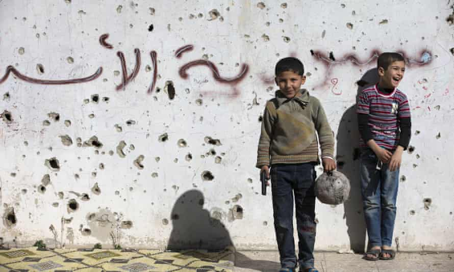 A Syrian boy holds a toy gun as he plays football between destroyed buildings in the old city of Homs.