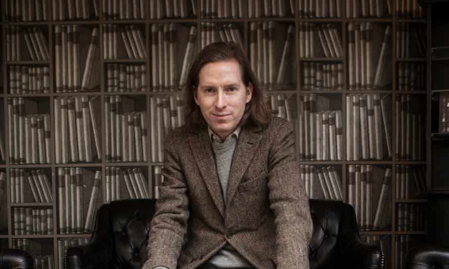 Director Wes Anderson sitting in front of library-inspired wallpaper in London in 2014.