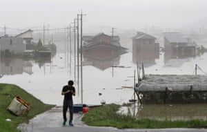 A man stands next to a flooded residential area in Kurashiki