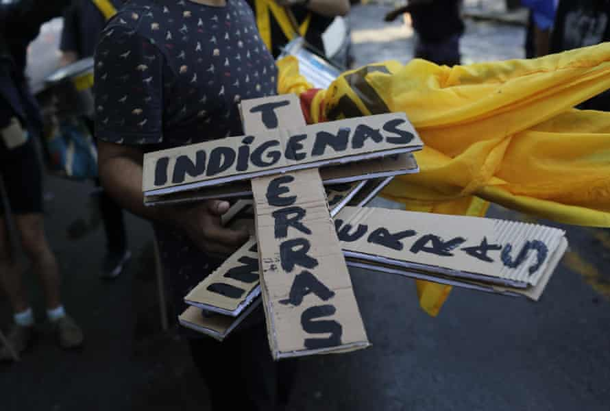A person holds cardboard crosses that read 'indigenous land' during a protest against budget cuts on public education by President Jair Bolsonaro's government.