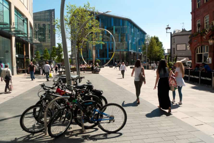 Bikes parked in Cardiff City Centre with a view of the Central Library and sculpture Cardiff, Wales