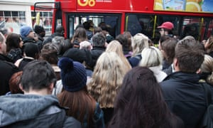People attempt to board a packed bus in Finsbury Park, north London.
