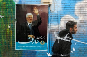 A man walks past a campaign poster of lead reformist candidate Mohmmad Reza Aref.