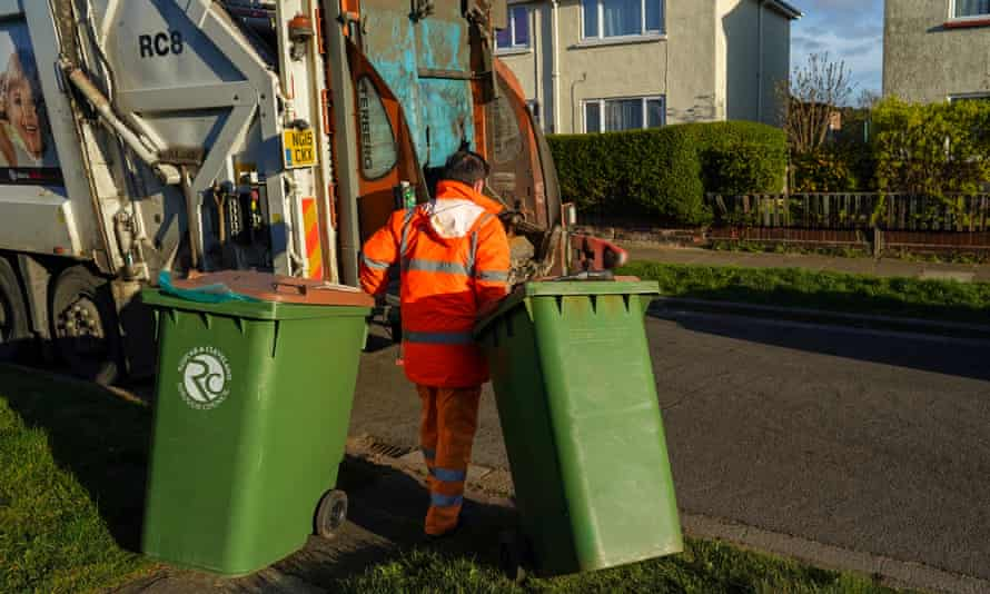 A refuse collector from Redcar and Cleveland Council works to empty bins in the streets of Saltburn during the first coronavirus lockdown in the UK, in March.
