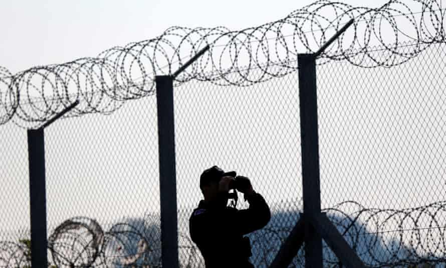A policeman on lookout at the Hungary- Serbia border fence ... in 1989 there were 15 border walls globally; today there are 70.