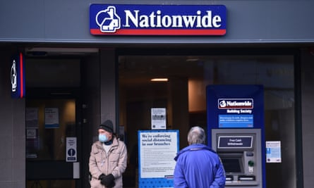A man wearing a face mask stands outside a Nationwide branch