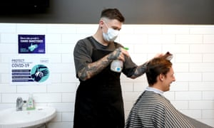 A barber wearing a face mask works on a customer's hair in Auckland