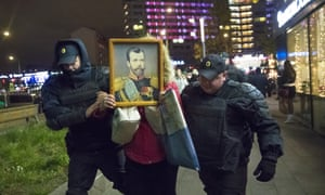 Police officers detain an Orthodox protester carrying a portrait of Nicholas II outside a cinema in Moscow.