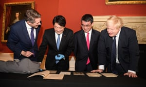 Gavin Williamson (left), Itsunori Onodera (2nd left), Taro Kono (2nd right) and Boris Johnson examine a selection of historical naval artifacts in the Queen's House gallery in Greenwich.