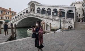 A tourist in a facemask at the Rialto bridge in Venice.