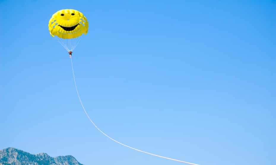 A girl parasailing under a yellow parachute with a smiley face