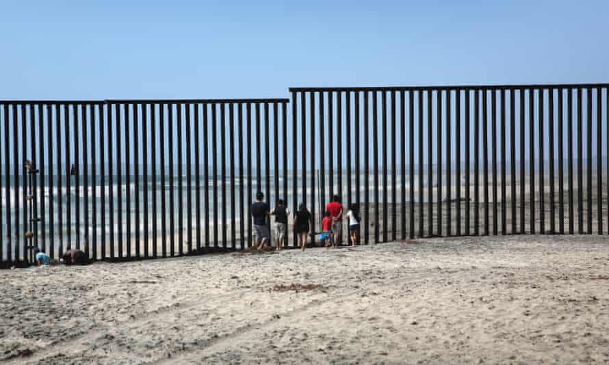 Mexicans stand on the beach while looking through the US-Mexico border fence into the United States in Tijuana.