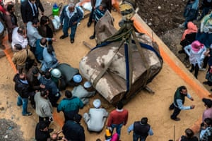 Egyptian workers excavate the statue