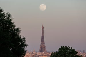 The supermoon rises over the Eiffel Tower in Paris, France.
