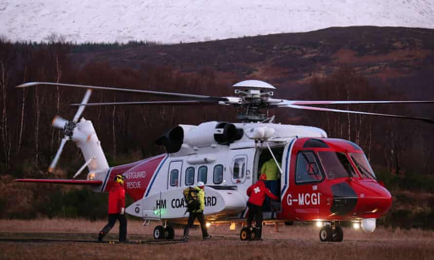 three figures in bright red/yellow jackets walk towards the door of a Mountain Rescue Helicopter; in the background a dark hillside and snowy slope.