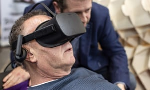 "Dutch designer Alexander Bannink explains how the ""Sarco"" euthanasia pod works to a man via virtual reality goggles."