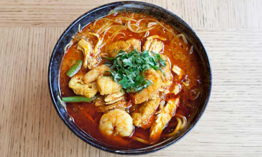 Chicken and prawn laksa in a round blue bowl