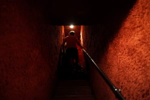 A man walks up a narrow staircase leading to a bar
